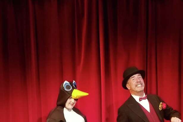 Mr. Popper (Bob Filipowich) takes his penguin Captain Cook (Alexis Taylor) out for a stroll.