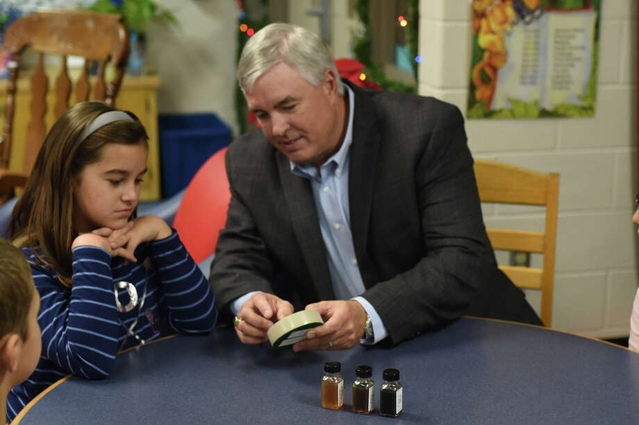 Parsley Energy's Mark Timmons, Vice President of Field Operations, shows a rock sample to fifth grader Alexia Cardona at General Tommy Franks Elementary while kicking off a partnership supporting MISD's Science, Technology, Engineering, and Math (STEM) programs Dec. 7, 2017. James Durbin/Reporter-Telegram Photo: James Durbin