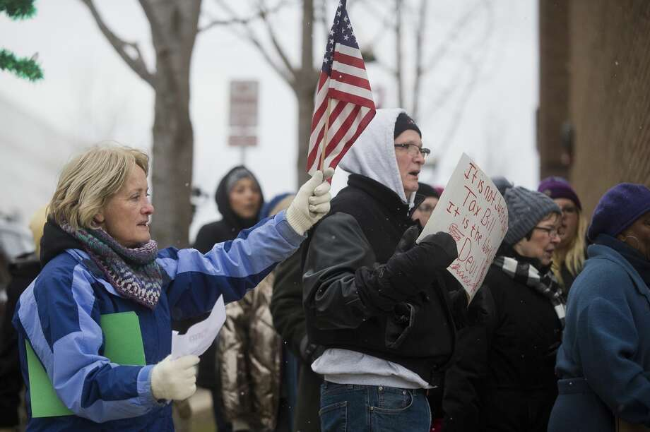 A group walks to U.S. Rep. John Moolenaar's Midland office during a protest of the GOP tax plan on Thursday, Dec. 7, 2017. (Katy Kildee/kkildee@mdn.net) Photo: (Katy Kildee/kkildee@mdn.net)