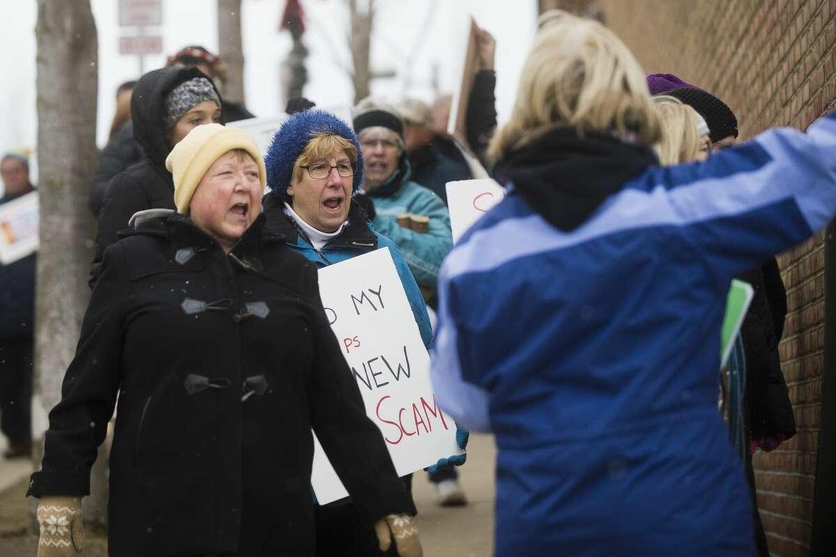 A group walks to U.S. Rep. John Moolenaar's Midland office during a protest of the GOP tax plan on Thursday, Dec. 7, 2017. (Katy Kildee/kkildee@mdn.net)