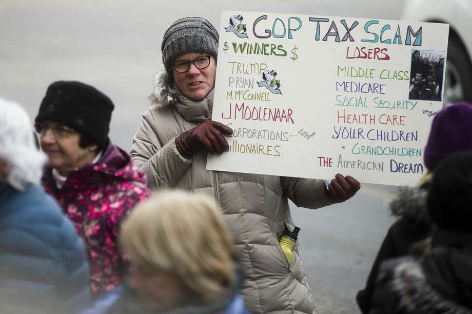 A group walks to U.S. Rep. John Moolenaar's Midland office during a protest of the GOP tax plan on Thursday, Dec. 7, 2017. (Katy Kildee/kkildee@mdn.net) Photo: (Katy Kildee/kkildee@mdn.net)