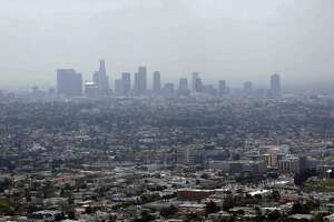 FILE - In this April 28, 2009 file photo, smog covers downtown Los Angeles. Attorney General Xavier Becerra announced, Thursday, Dec. 7, 2017, that California is among fourteen states and the District of Columbia that are suing the Trump administration over what they say is a failure to enforce smog standards. (AP Photo/Nick Ut, File)
