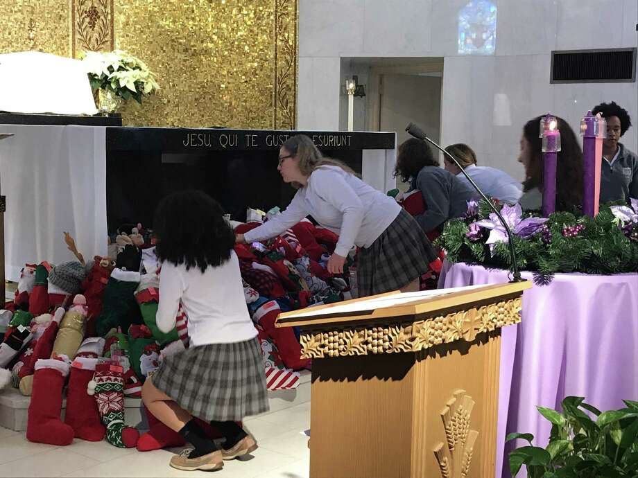 Around 600 homemade stockings, stuffed to the brim with hats, games, coloring books and stuffed animals, were placed upon the altar Thursday morning at an all-girls Catholic high school in an annual act of kindness that has become a holiday tradition. Photo: By Jessica Lerner