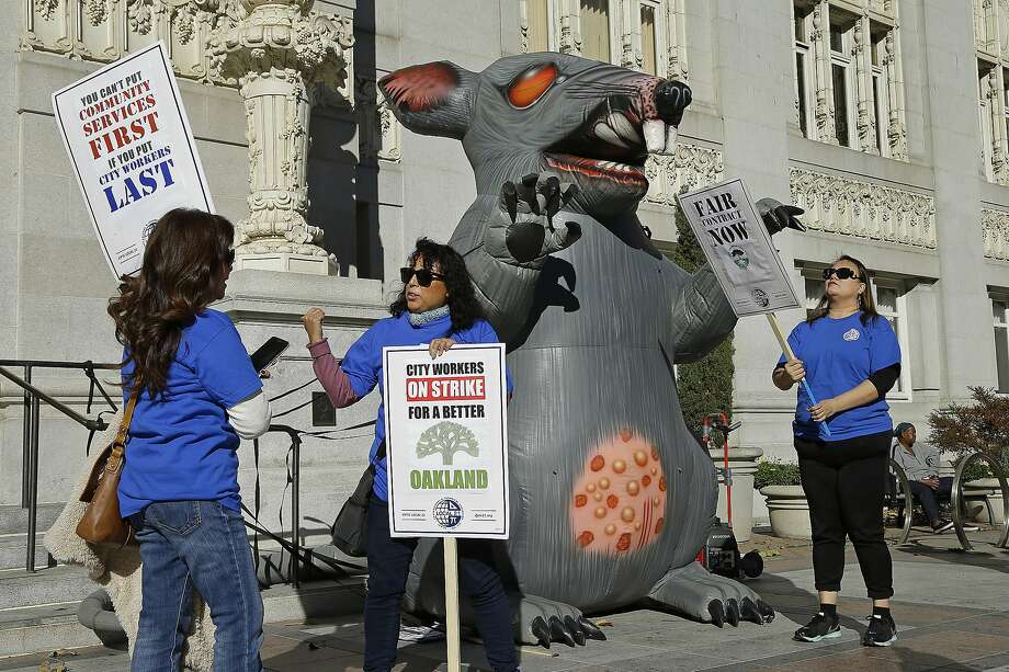 Oakland city workers picket beside an inflatable rat in front of City Hall on Tuesday. Photo: Ben Margot, Associated Press
