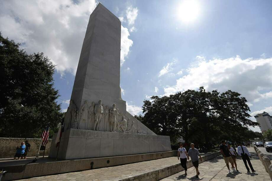 Visitors walk past the Cenotaph near Alamo Plaza after a rally to keep the monument in place in October 2017. Members of the Alamo Defenders Descendants Association were protesting the proposed removal of the Cenotaph under the Alamo master plan. Photo: Kin Man Hui /San Antonio Express-News / ©2017 San Antonio Express-News