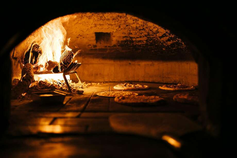 Pizzas cook in the wood-fired brick oven at Tommaso's in San Francisco. Photo: Mason Trinca, Special To The Chronicle