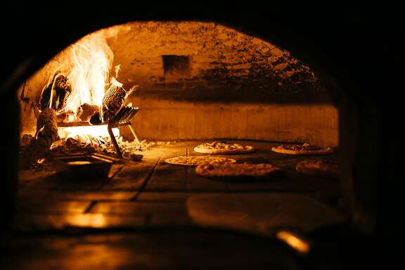 Pizzas cook in the wood-fired brick oven at Tommaso's in San Francisco, Calif. Wednesday, December 6, 2017.