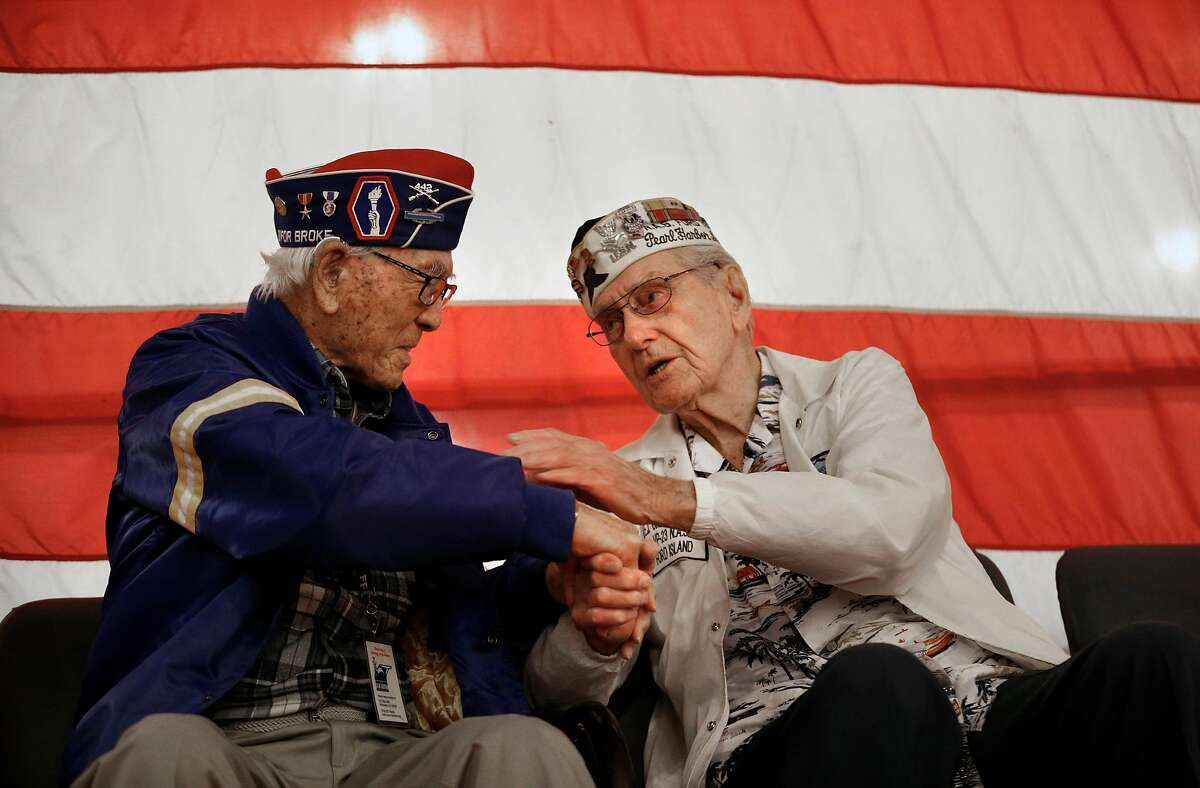 """Army veteran Lawson Sakai, (left) and Navy veteran and Pearl Harbor survivor E.J. """"Chuck"""" Kohler share a moment during a ceremony on the 76th anniversary of the bombing of Pearl Harbor aboard the USS Hornet on Thursday December 7, 2017, in Alameda, Calif."""
