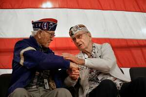 "Army veteran Lawson Sakai, (left) and Navy veteran and Pearl Harbor survivor E.J. ""Chuck"" Kohler share a moment during a ceremony on the 76th anniversary of the bombing of Pearl Harbor aboard the USS Hornet  on Thursday December 7, 2017, in Alameda, Calif."