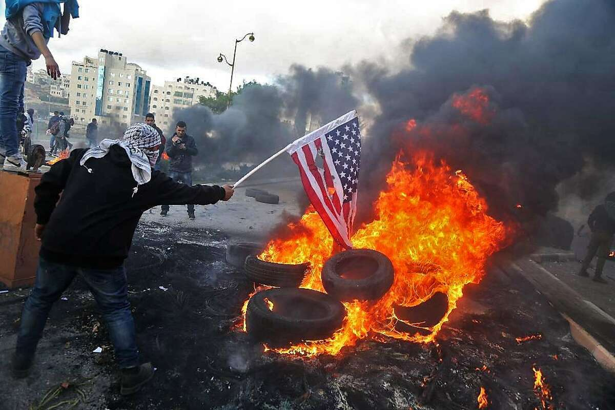 TOPSHOT - A Palestinian protester sets alight an America flag during clashes with Israeli troops at a protest against US President Donald Trump's decision to recognize Jerusalem as the capital of Israel, near the Jewish settlement of Beit El, near the West Bank city of Ramallah on December 7, 2017. / AFP PHOTO / ABBAS MOMANIABBAS MOMANI/AFP/Getty Images