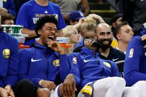 Golden State Warriors' Quinn Cook and Kevin Durant laugh after David West and Orlando Magic's Marreese Speights scuffled in 4th quarter of Warriors' 110-100 win during NBA game at Oracle Arena in Oakland, Calif., on Monday, November 13, 2017.
