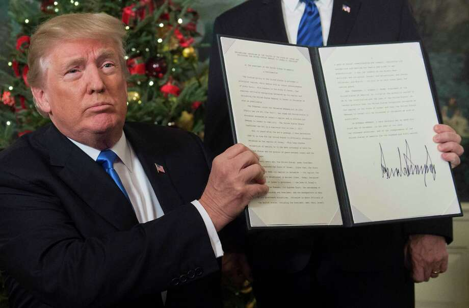 """President Donald Trump holds up a signed memorandum recognizing Jerusalem as Israel's capital at the White House on Wednesday. """"It's the right thing to do,"""" he said. Photo: SAUL LOEB, Contributor / AFP or licensors"""