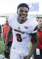 Louisville quarterback Lamar Jackson smiles as he leaves the field after his team defeated Kentucky 44-17 in an NCAA college football game Saturday, Nov. 25, 2017, in Lexington, Ky. (AP Photo/David Stephenson)