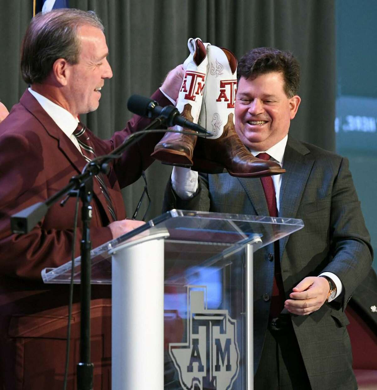 Jimbo Fisher, left, holds up a pair of Texas A&M cowboy boots next to Texas A&M athletic director Scott Wooward after being introduced as the Aggies' new NCAA college football coach Monday, Dec. 4, 2017, in College Station, Texas.