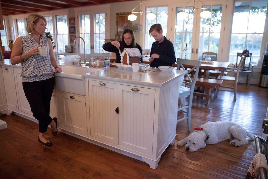 Sonya Sweeney, whose family lost its home during the recent fires in Wine Country, looks on after serving breakfast as her son Nicky, 12, and daughter Maddie, 15, make a gingerbread house for a fundraiser at their temporary residence while they wait to move into a newly purchased house in Sebastopol. Photo: Peter DaSilva, Special To The Chronicle