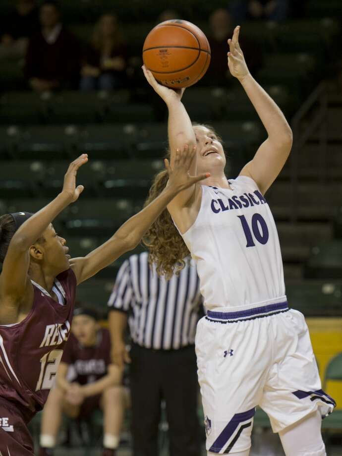Midland Classical Academy's Leia Beatte pulls up for a shot as Lee High's Destiny Stanford tries to get over to block her 12/07/17  in the opening game of the Tall City Oilman's Invitational at the Chaparral Center. Tim Fischer/Reporter-Telegram Photo: Tim Fischer/Midland Reporter-Telegram