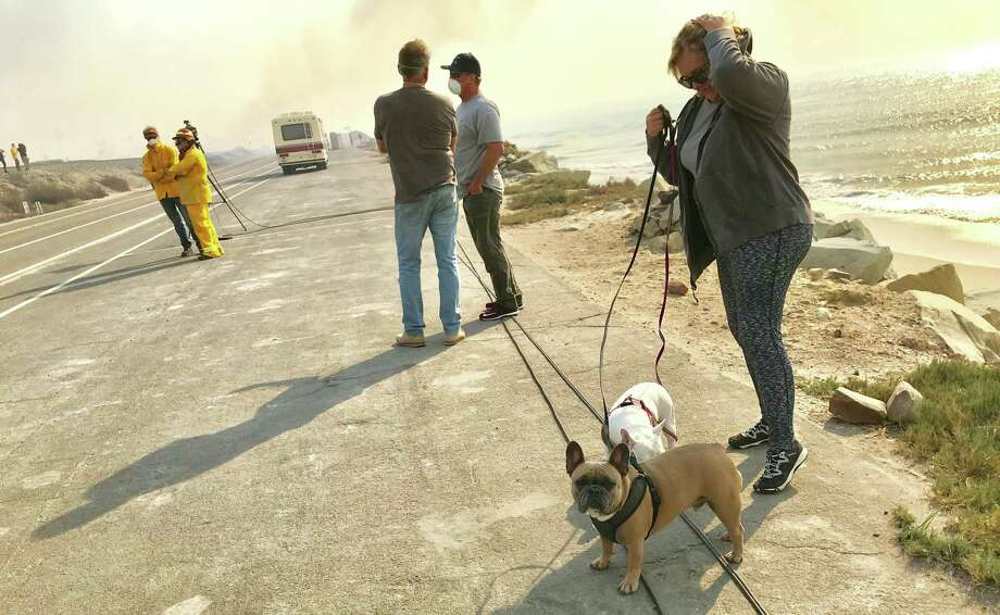 Gina Haase walks the family pooches in Faria Beach, Ventura County, on Dec. 7, 2017, after finding out her home survived the Thomas Fire. Photo: Steve Rubenstein / The Chronicle / /