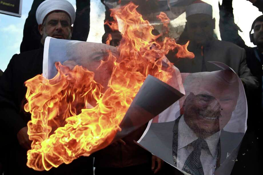 Palestinians burn posters of Israeli prime minister Benjamin Netanyahu and U.S. President Donald Trump, during a protest against the U.S. decision to recognize Jerusalem as Israel's capital, in Gaza City Thursday, Dec. 7, 2017. (AP Photo/ Khalil Hamra) Photo: Khalil Hamra, STF / Copyright 2017 The Associated Press. All rights reserved.