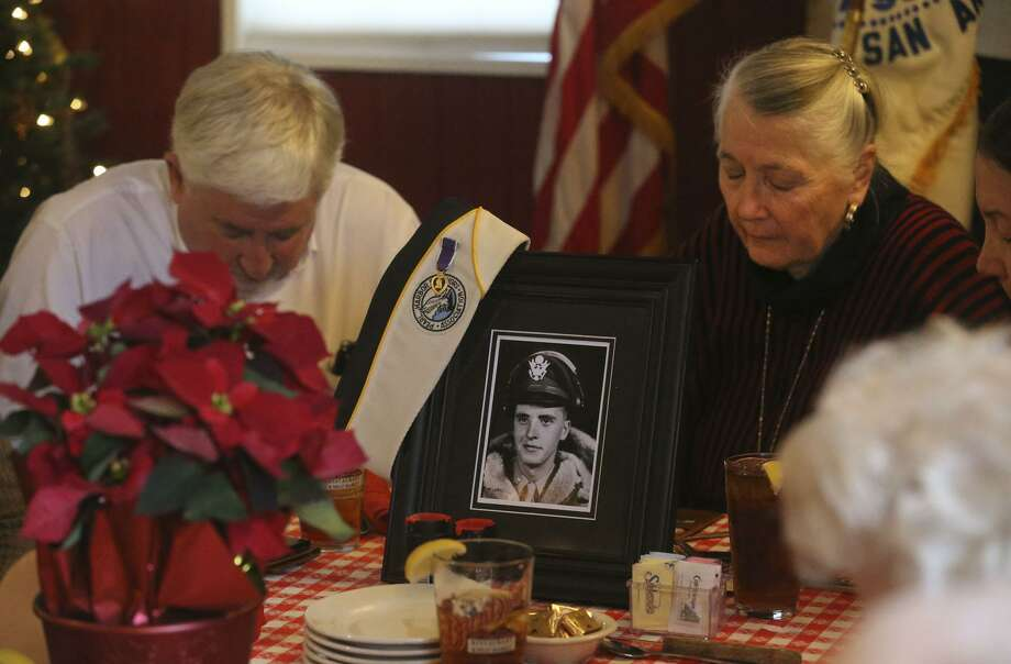 Sandra Anderson Mathis (right) bows her head in silence Thursday December 7, 2017 at a lunch held at the Barn Door restaurant in honor of Pearl Harbor survivors. Mathis' father (pictured) was Richard Anderson who survived the attack on Pearl Harbor and later in the war became a B-24 bomber pilot. Richard Anderson passed away last October. Pearl Harbor was attacked by the Japanese December 7, 1941. Photo: John Davenport, STAFF / San Antonio Express-News / ©John Davenport/San Antonio Express-News