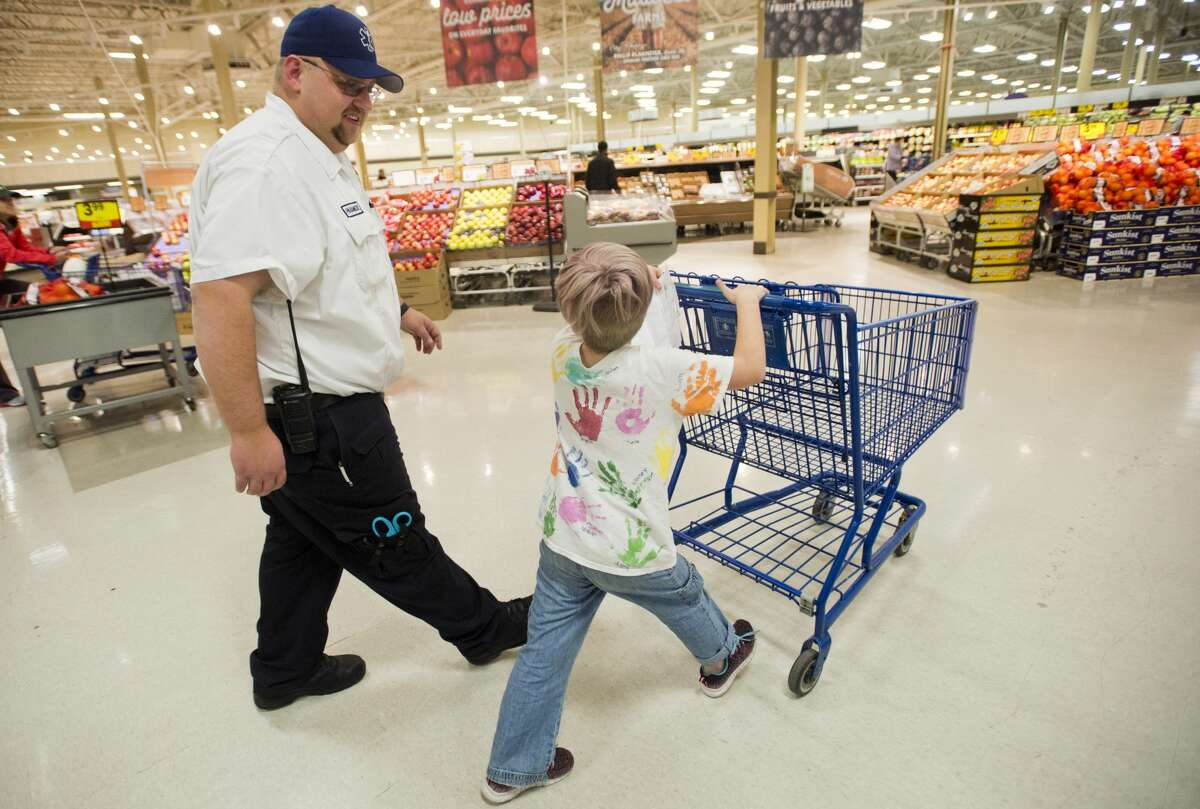 Marc Thrush, a paramedic with MidMichigan Medical Center, walks toward the toy section with Lexia Schmidt of Midland, 7, during the annual Shop with a Hero event on Wednesday, Dec. 6, 2017 at Meijer. The store donates $100 gift cards to the children, who can buy Christmas gifts for whomever they choose. (Katy Kildee/kkildee@mdn.net)