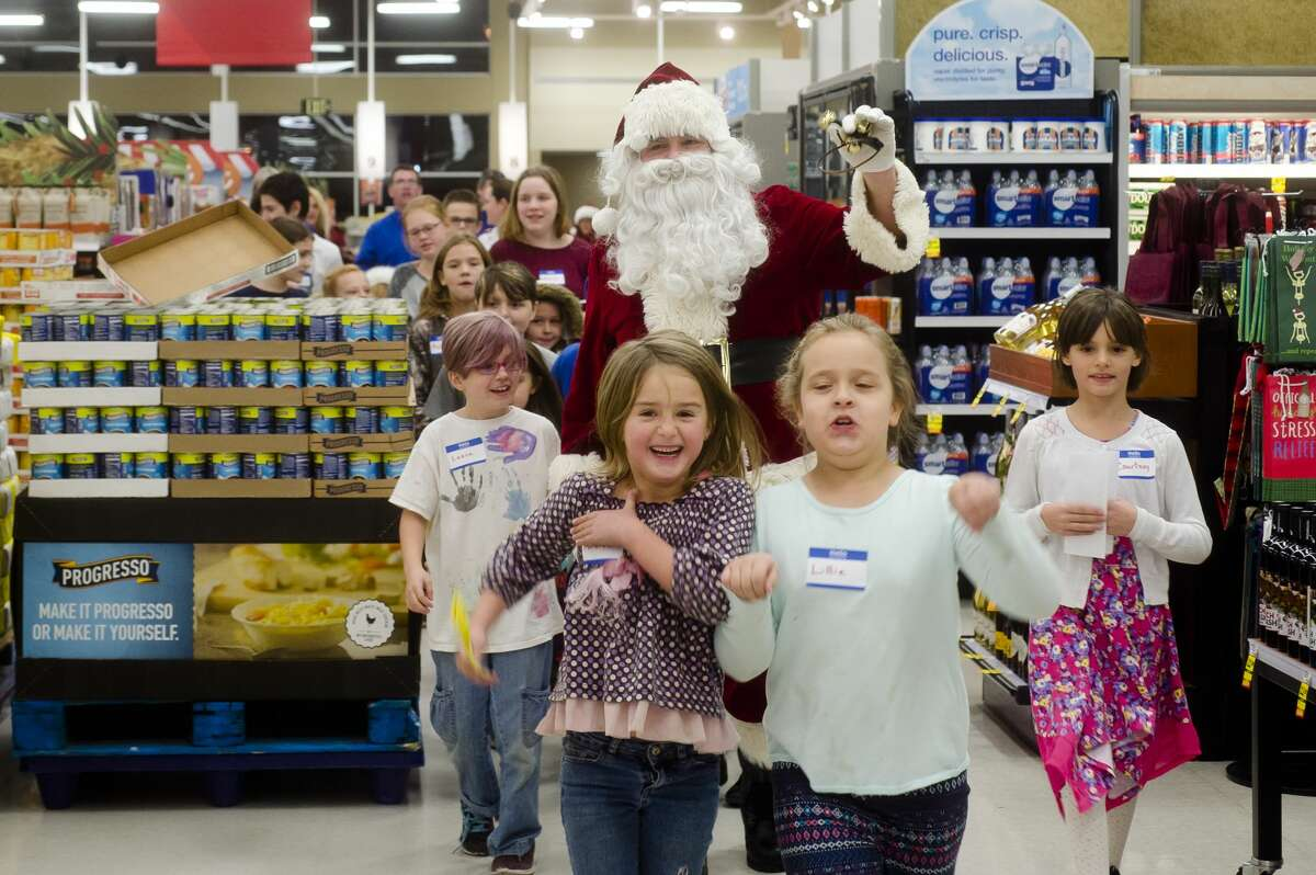 Santa Claus arrives before a group of children participate in the annual Shop with a Hero event on Wednesday, Dec. 6, 2017 at Meijer. The store donates $100 gift cards to the children, who can buy Christmas gifts for whomever they choose. (Katy Kildee/kkildee@mdn.net)