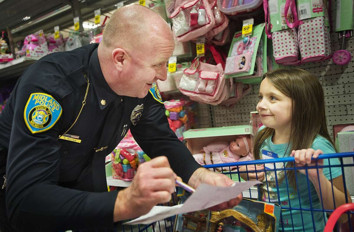 Rodney Roten, deputy chief of the Midland Police Department, helps Autumn Stillwagon of Midland, 7, to find the items on her shopping list during the 18th annual Shop with a Hero event on Wednesday, Dec. 6, 2017 at Meijer. The store donates $100 gift cards to the children, who can buy Christmas gifts for whomever they choose. (Katy Kildee/kkildee@mdn.net)