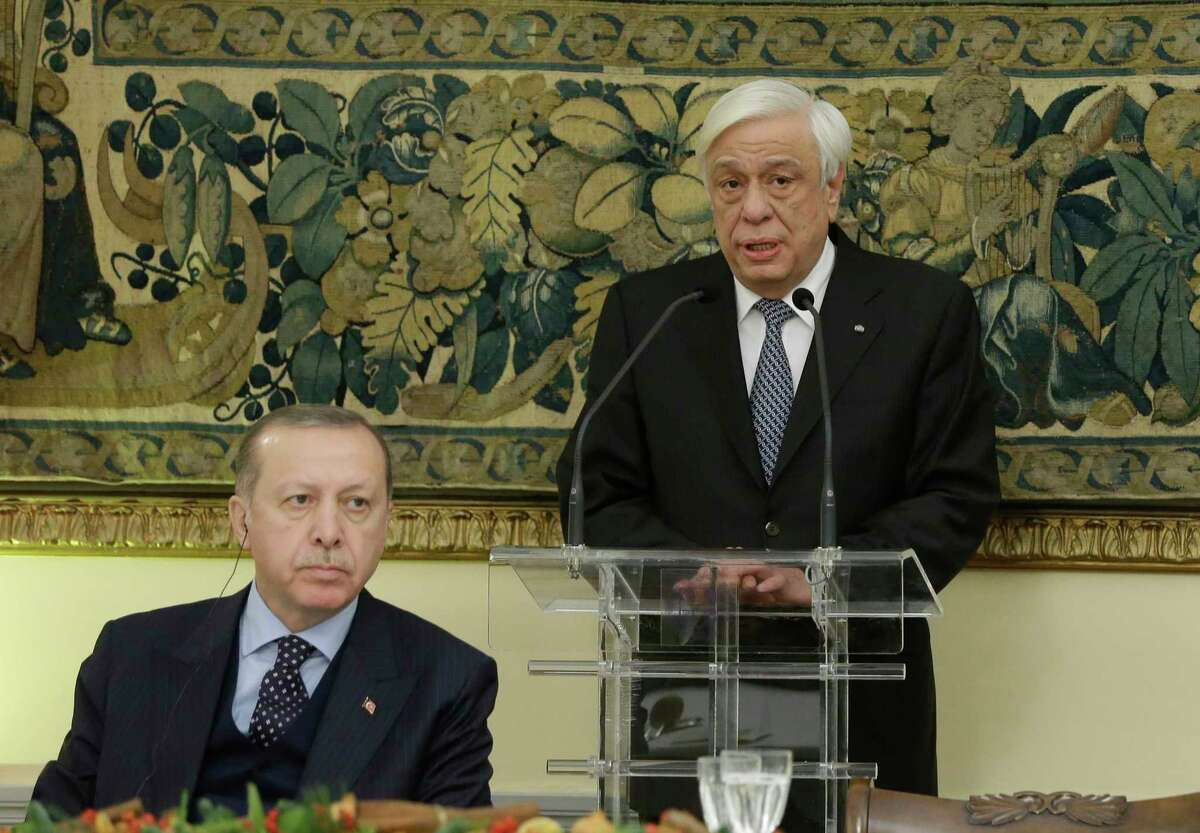 Greece's President Prokopis Pavlopoulos, right, delivers a speech as Turkey's President Recep Tayyip Erdogan, left, listens during an official dinner in Athens, Thursday, Dec. 7, 2017. The presidents engaged in a thinly-veiled verbal spat over the treaty and the Muslim minority in northeastern Greece, when they met earlier in the day, a tense start for the first official visit by a Turkish president to Greece in six decades. (AP Photo/Thanassis Stavrakis)