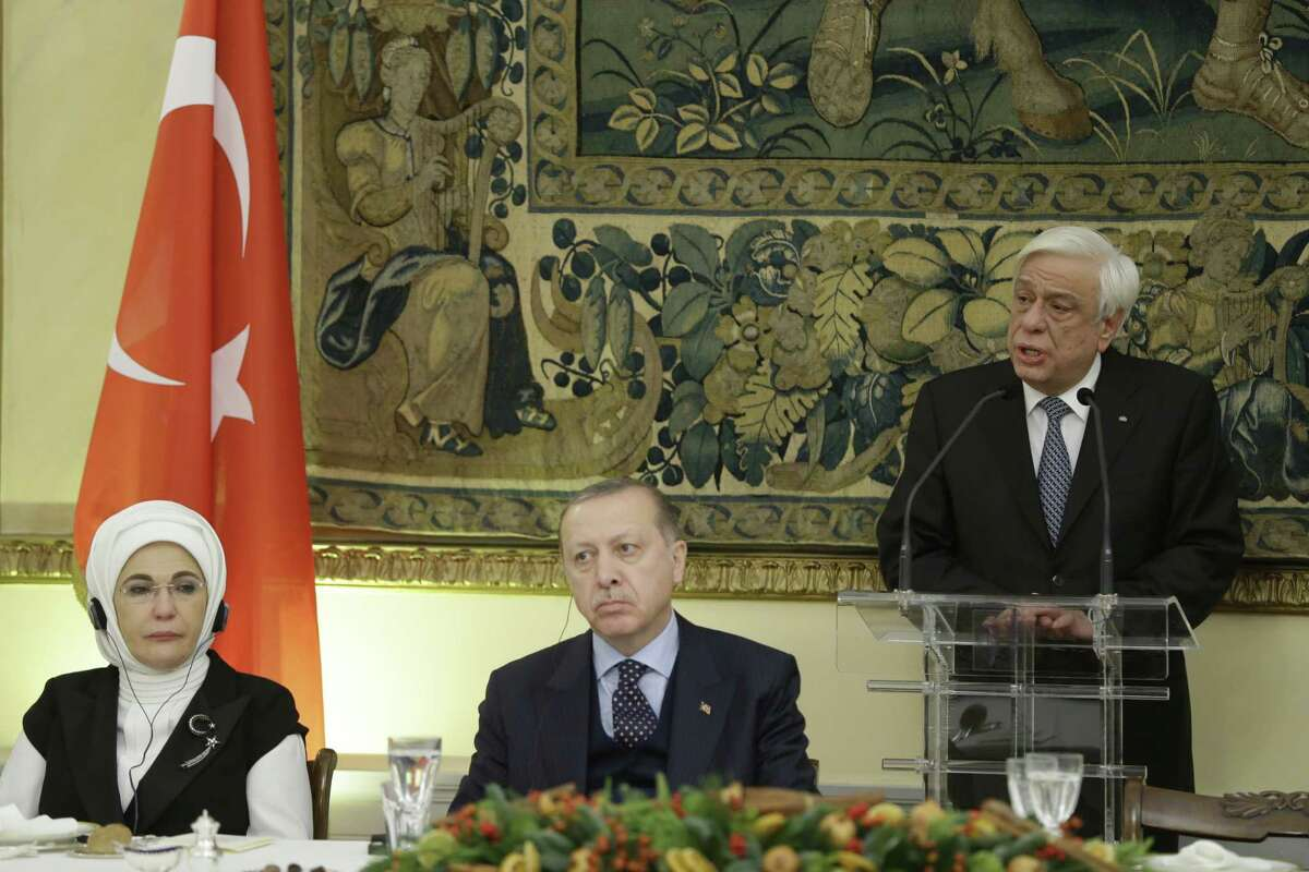 Greece's President Prokopis Pavlopoulos, right, delivers a speech as Turkey's President Recep Tayyip Erdogan, centre and his wife Emine, participate ant an official dinner in Athens, Thursday, Dec. 7, 2017. The presidents engaged in a thinly-veiled verbal spat over the treaty and the Muslim minority in northeastern Greece, when they met earlier in the day, a tense start for the first official visit by a Turkish president to Greece in six decades. (AP Photo/Thanassis Stavrakis)