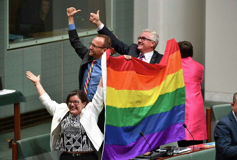 Members of parliament, from left, Cathy McGowan, Adam Brandt and Andrew Wilkie celebrate the passing of the Marriage Amendment Bill in the House of Representatives at Parliament House in Canberra, Thursday, Dec. 7, 2017. Gay marriage was endorsed by 62 percent of Australian voters who responded to a government-commissioned postal ballot by last month. (Mick Tsikas/AAP Image via AP) Photo: Mick Tsikas, SUB / AAP