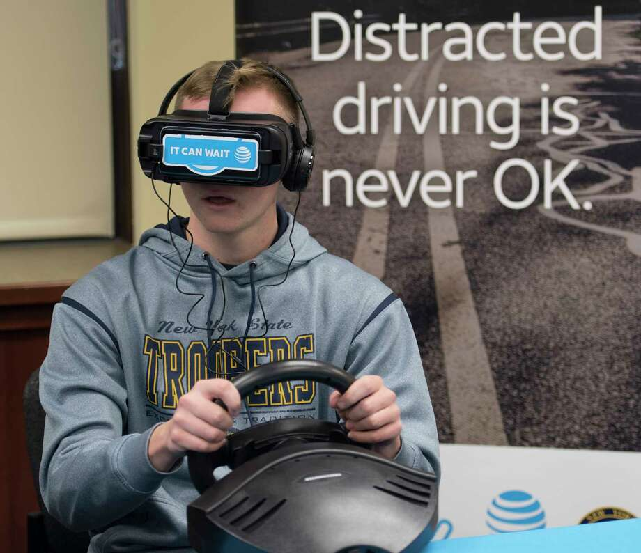 Shawn Johnstone, consumer service representative, tries on one of the 10 donated It Can Wait Virtual Reality Simulators Thursday Dec 7, 2017 at the New York State Police Academy in Albany, NY.  AT&T has contributed 10 3D virtual reality simulators to the New York State Trooper Foundation.  This educational tool will be used to provide a firsthand experience on has dangerous it is to take their eyes off the road due to distraction,  (Skip Dickstein/ Times Union) Photo: SKIP DICKSTEIN / 20042338A
