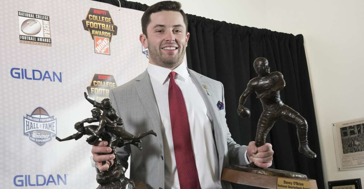 Oklahoma's Baker Mayfield holds the Davey O'Brien National Quarterback Award, right, and Walter Camp Player of the Year trophy during the College Football Awards show at the College Football Hall of Fame, Thursday, Dec. 7, 2017, in Atlanta. (AP Photo/John Amis)