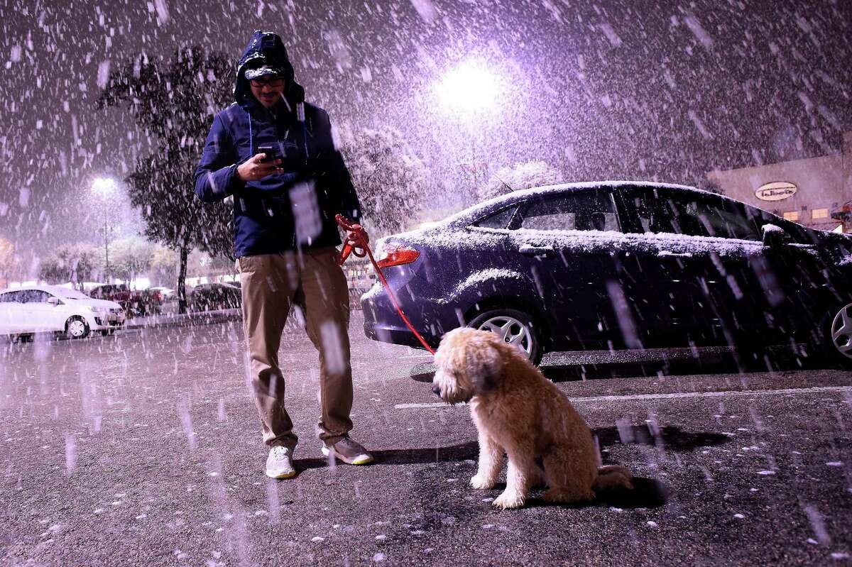 Matt Debrizzi and his dog, Huey, enjoy the snowfall near the intersection of Hurbner and Interstate 10 on Thursday night, Dec. 7.