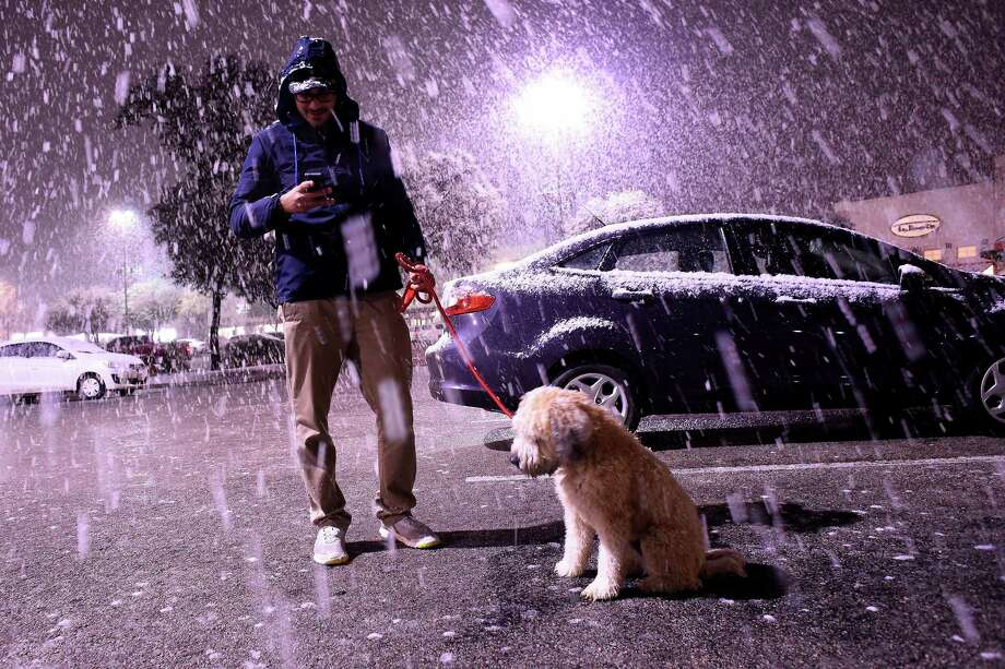 Matt Debrizzi and his dog, Huey, enjoy the snowfall near the intersection of Hurbner and Interstate 10 on Thursday night, Dec. 7. Photo: Billy Calzada /San Antonio Express-News / San Antonio Express-News