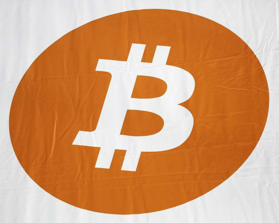 """FILE - In this Monday, April 7, 2014, file photo, a bitcoin logo is displayed at the Inside Bitcoins conference and trade show in New York. The bitcoin miner NiceHash says it is investigating a security breach and the theft of the contents of the NiceHash """"bitcoin wallet."""" The company said Thursday, Dec. 7, 2017 in a statement posted on its website that it had stopped operations and was working to verify how many bitcoins were taken. (AP Photo/Mark Lennihan, File) Photo: Mark Lennihan, STF / Copyright 2017 The Associated Press. All rights reserved."""
