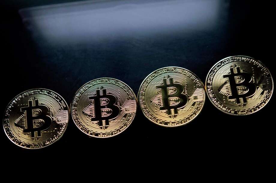 "Bitcoin is a digital currency that is not tied to a bank or government and allows users to spend money anonymously. The coins are created by users who ""mine"" them by lending computing power to verify other users' transactions. They receive bitcoins in exchange. The coins also can be bought and sold on exchanges with U.S. dollars and other currencies. Photo: JUSTIN TALLIS, Contributor / AFP or licensors"