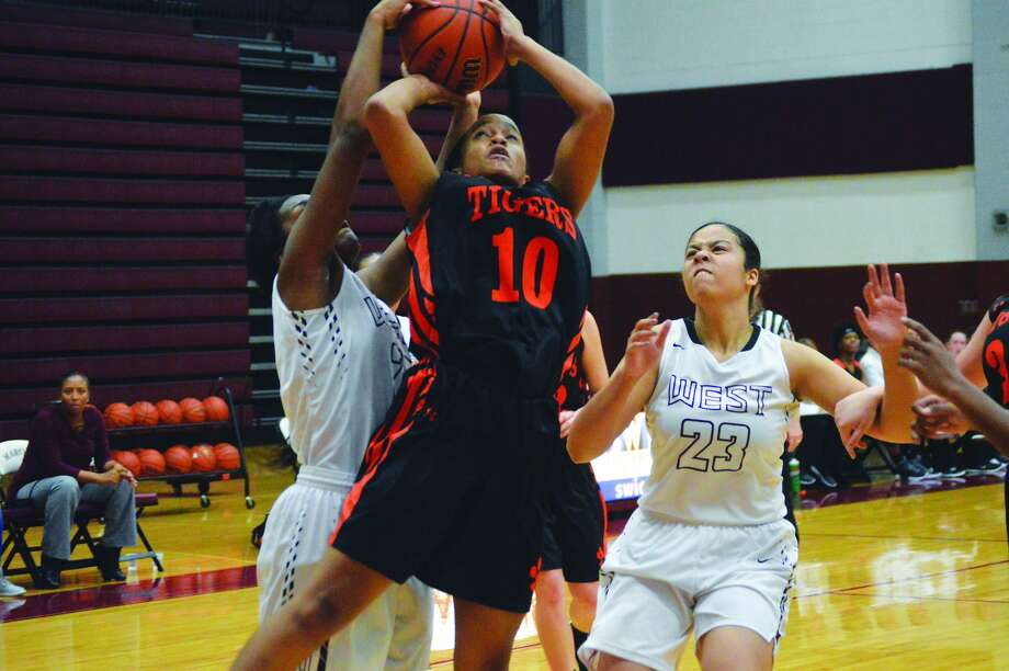 Edwardsville junior forward Jaylen Townsend (No. 10) goes up for a shot with two Belleville West defenders guarding her during the first quarter of Thursday's conference game.