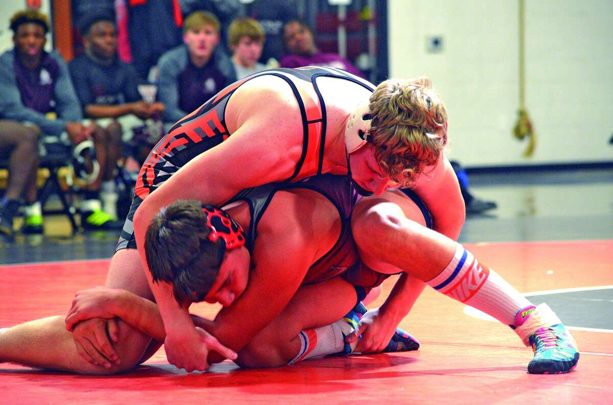 Edwardsville junior Sam Martin, top, tries to get a hold on Belleville West's Riley Elam in a 195-pound match during Thursday's Southwestern Conference match at Jon Davis Wrestling Center.