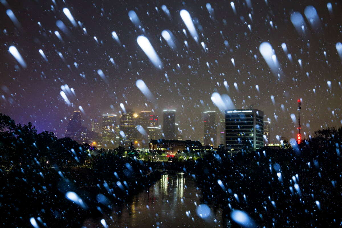 Snow falls in front of downtown Houston Thursday, Dec. 7, 2017.