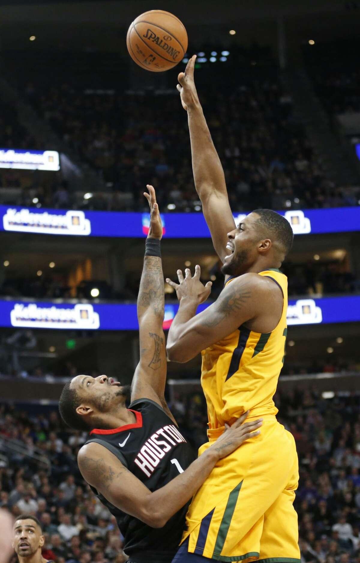 Utah Jazz forward Derrick Favors, right, shoots as Houston Rockets forward Trevor Ariza (1) defends during the second half of an NBA basketball game Thursday, Dec. 7, 2017, in Salt Lake City. (AP Photo/Rick Bowmer)