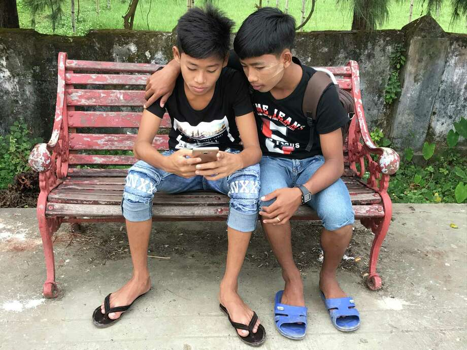A pair of teenagers with smartphones in Sittwe, Myanmar. Almost no one had a smartphone in Myanmar four years ago, but now they're ubiquitous, and many access the internet through Facebook. Photo: Washington Post Photo By Annie Gowen. / The Washington Post