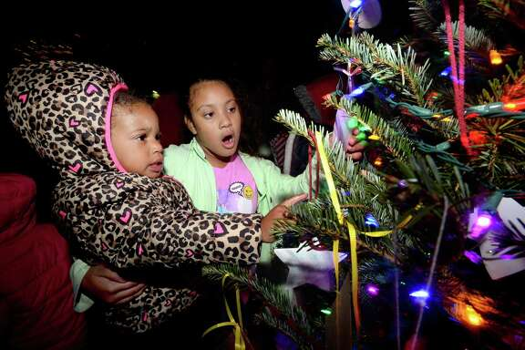 Khymonie Gallo (left) and Alexis Victoria take in the ornaments hanging amid the lights at the City of Beaumont's annual downtown tree lighting Thursday. Pre-lighting activities, including letters to the No rth Pole, crafts and visits with Santa, were held inside the Art Museum of Southeast Texas due to the weather.  Photo taken Thursday, December 7, 2017 Kim Brent/The Enterprise