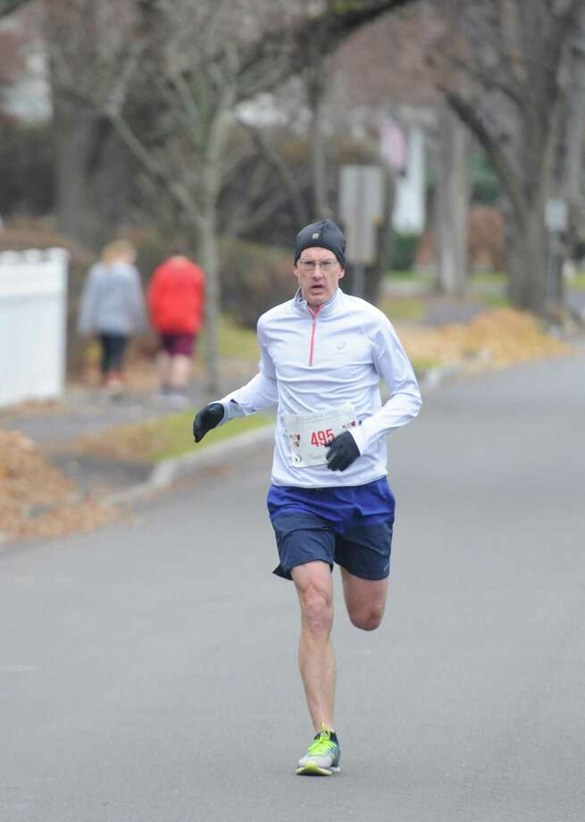 First-place finisher Ed Banks, of Darien, runs down the final stretch in the 30th Annual William Raveis Jingle Bell Jog in Greenwich, Conn. Sunday, Dec. 3, 2017. Presented by Threads & Treads, the race took costume-clad runners along a 3-mile course beginning a the YMCA and traveling north by the Brunswick School and Greenwich Academy campuses. Photo: Tyler Sizemore / Hearst Connecticut Media / Greenwich Time