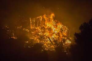 BONSALL, CA - DECEMBER 08:  A house burns in the Lilac Fire in the early morning hours of December 8, 2017 near Bonsall, California. Strong Santa Ana winds are pushing multiple wildfires across the region, expanding across tens of thousands of acres and destroying hundreds of homes and structures.  (Photo by David McNew/Getty Images)