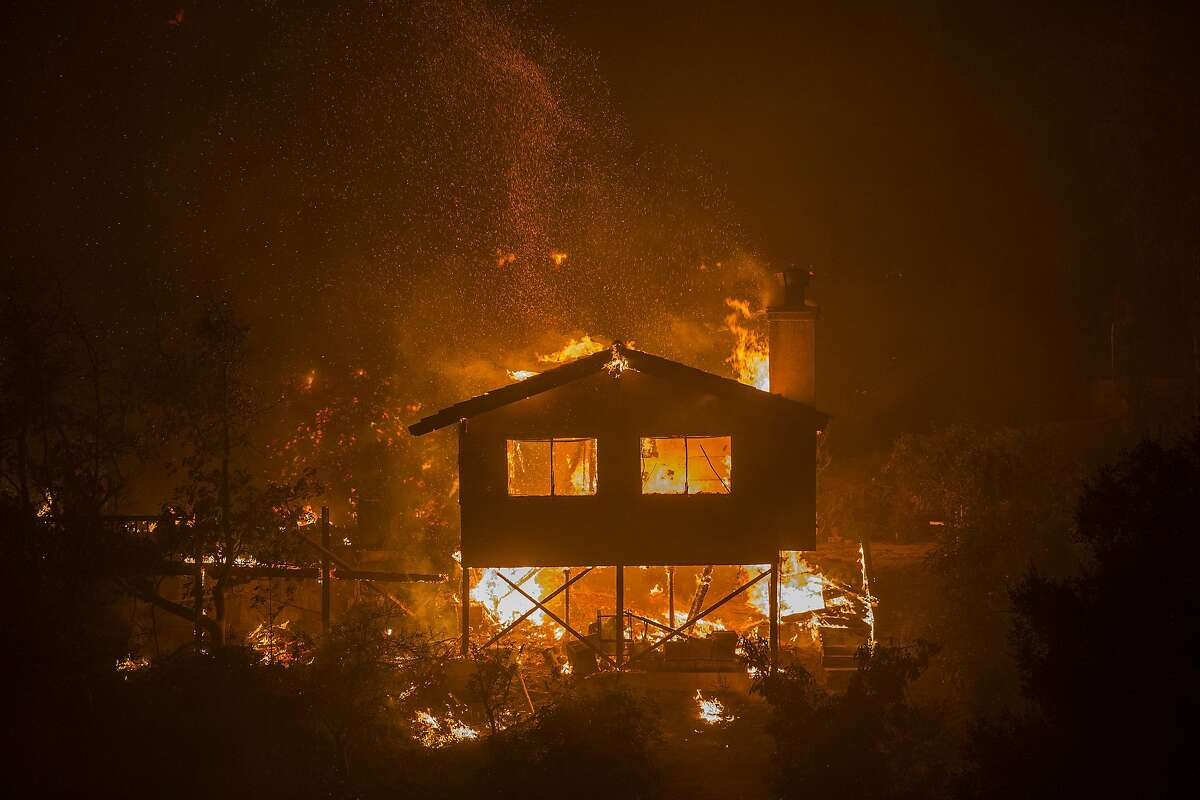 A structure burns at the Lilac Fire in the early morning hours of December 8, 2017 near Bonsall, California. Strong Santa Ana winds are pushing multiple wildfires across the region, expanding across tens of thousands of acres and destroying hundreds of homes and structures.