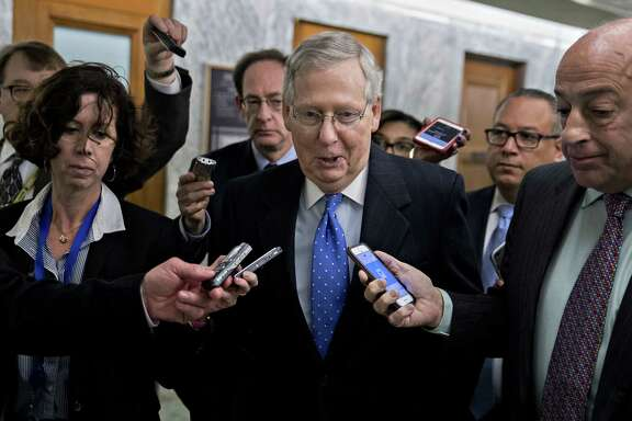 Senate Majority Leader Mitch McConnell, R-Ky. (center) walks through the Dirksen Senate Office building after speaking at a news conference on tax reform in Washington on Nov. 30, 2017. MUST CREDIT: Bloomberg photo by Andrew Harrer.