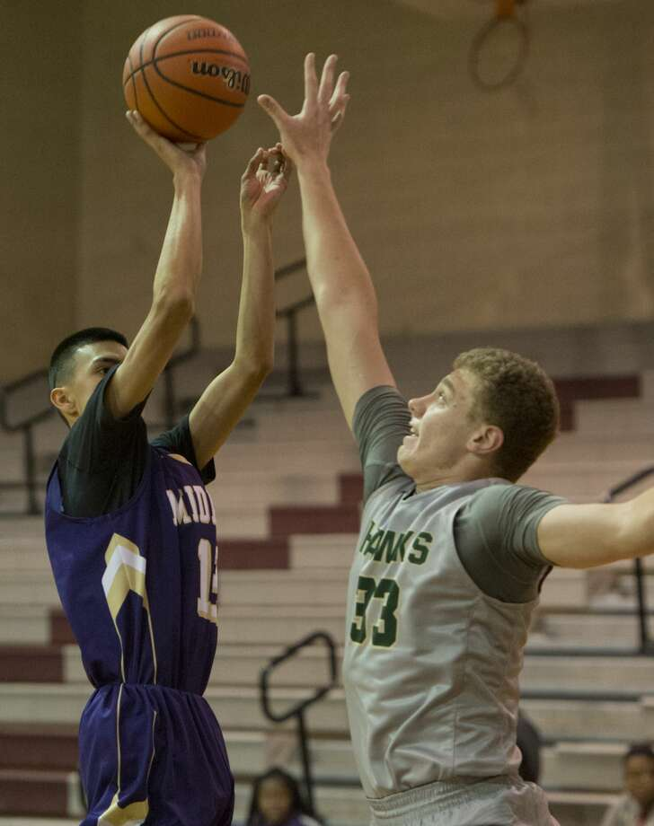 Midland High's Nicholas Terrazas puts up a shot over Fort Worth Birdville's Tanner Rhodes 12/08/17 during a matchup in the Tall City Oilman's Invitational at Lee High gym. Tim Fischer/Reporter-Telegram Photo: Tim Fischer/Midland Reporter-Telegram