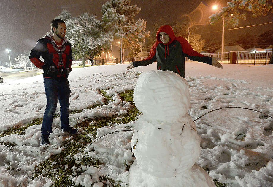 Lamar freshmen Chris Brewer (left) and Joey Dalager react as they take in the snowman they built at the entry to Cardinal Village as wintry conditions brought snow to the region Friday.  Photo taken Friday, December 8, 2017 Kim Brent/The Enterprise Photo: Kim Brent / BEN