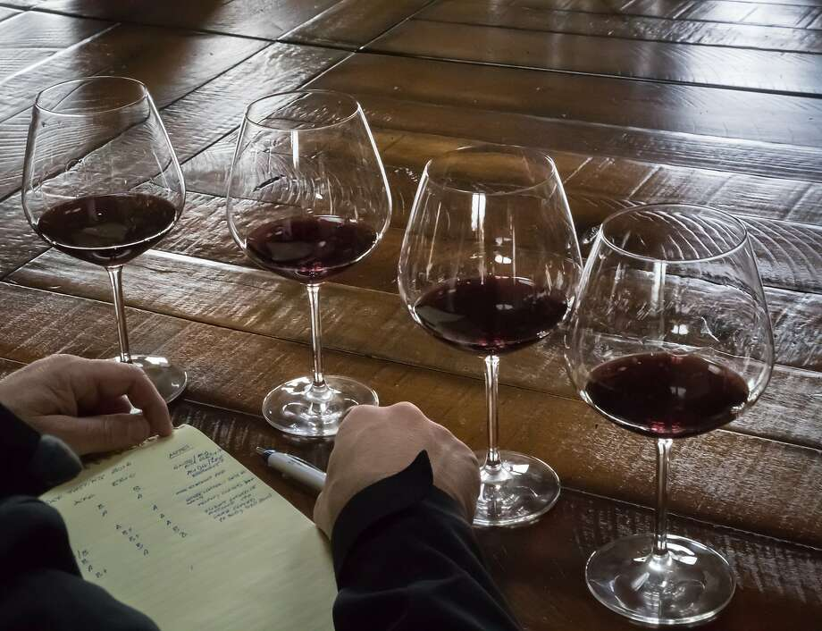 Javier Tapia take notes on wine samples at Rhys Vineyards. Photo: Paul Kuroda, Special To The Chronicle
