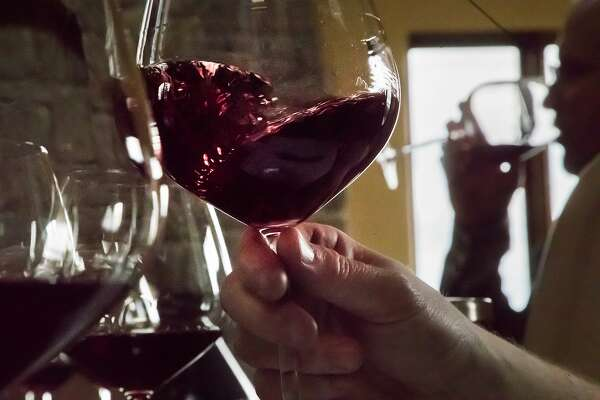 Winemaker Jeff Brinkman drawls oxygen into the wine during a tasting session with Rhys Winery owner Kevin Harvey in the background on Monday, Nov. 13, 2017 in Los Gatos, Calif.