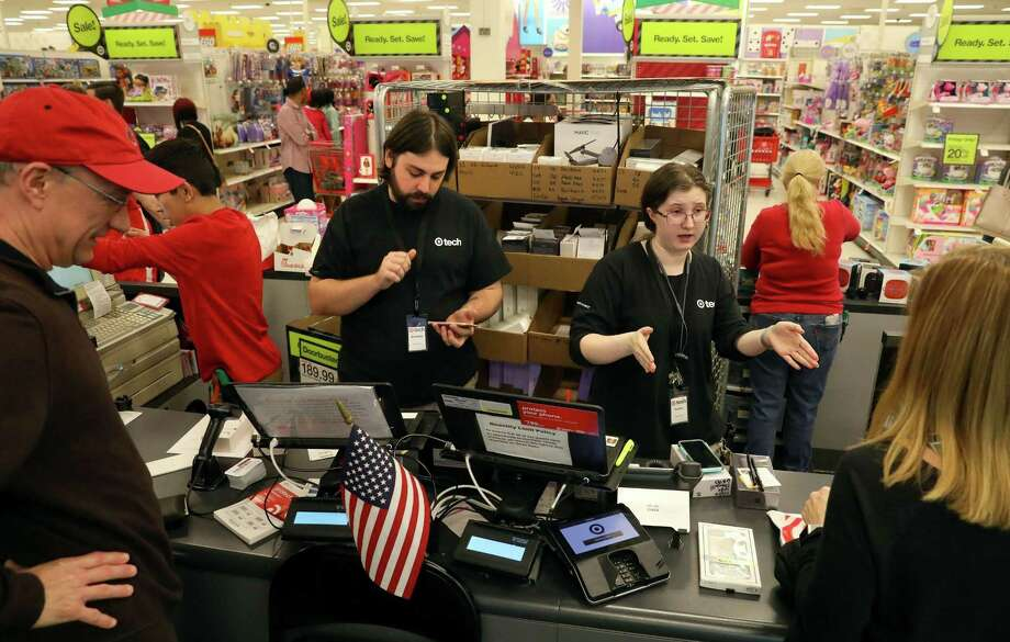 Angela Johannsen, right, and Brad Garrett, left, help customers in the tech department of Target on Friday, Nov. 24, 2017 in Ballwin, Mo. Target has said it will hire a record 100,000 temporary workers this holiday season. Experts say brick-and-mortar retailers hoping to fend off Amazon.com Inc. need to deploy the one weapon that could set them apart: top-notch customer service, provided by actual humans. Photo: Christian Gooden /Associated Press / St. Louis Post-Dispatch